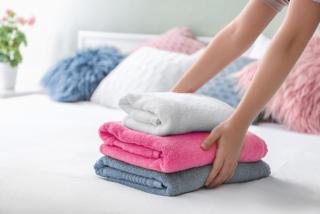 畳んであるタオルをベッドに置く画像