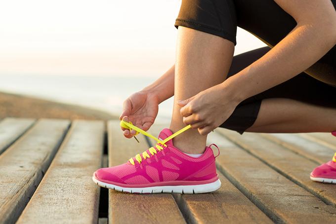 しゃがんで靴ひもを結んでいる女性の足元の画像