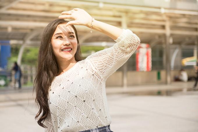 日差しを遮るために手を額にかざす女性の画像