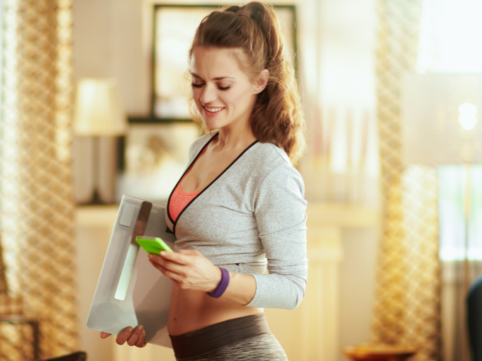 体重計を持っている女性の画像