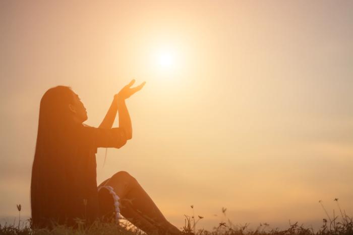 女性が空から光を受け取っているような写真