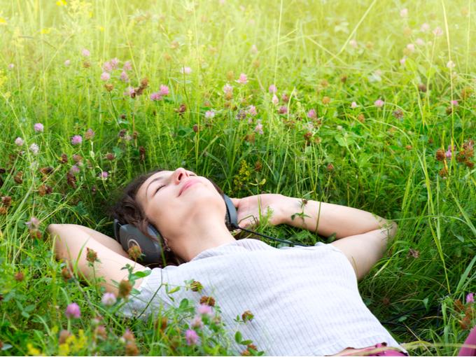原っぱで音楽を聴く女性の画像