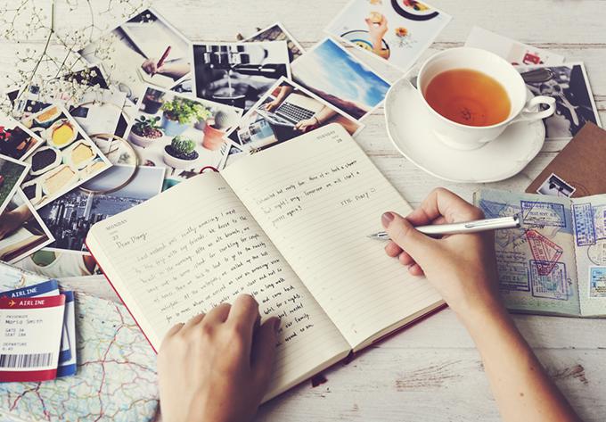 写真を広げて日記を書いている画像