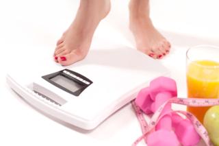 体重計に乗ろうとしている女性の画像