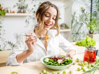 野菜たっぷりのサラダを食べる女性