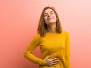 腹部を押さえる女性