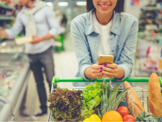 ショッピングカートを引きながらスマホを確認する女性の画像