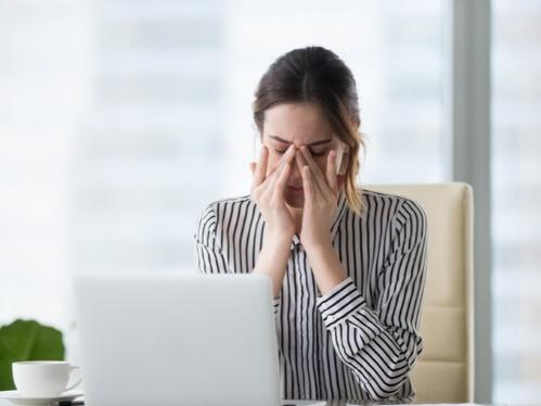 パソコンで眼精疲労の女性