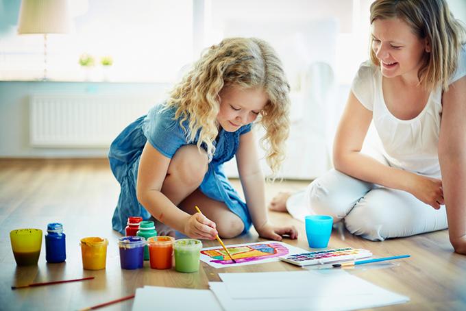 子どもの遊びを見守る女性の画像
