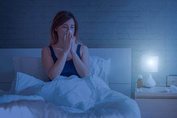 暗い部屋で鼻をかんでいるベッドの上の女性