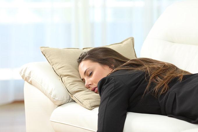 ソファの上でぐったりしている女性の画像