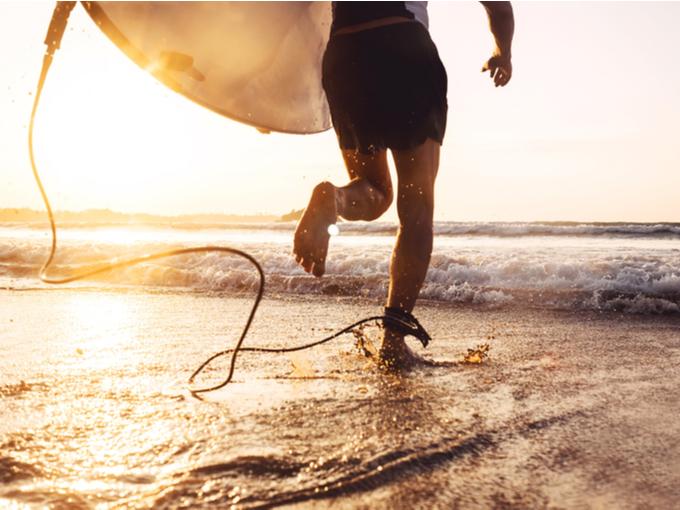 サーフィンをしようと海に出る男性