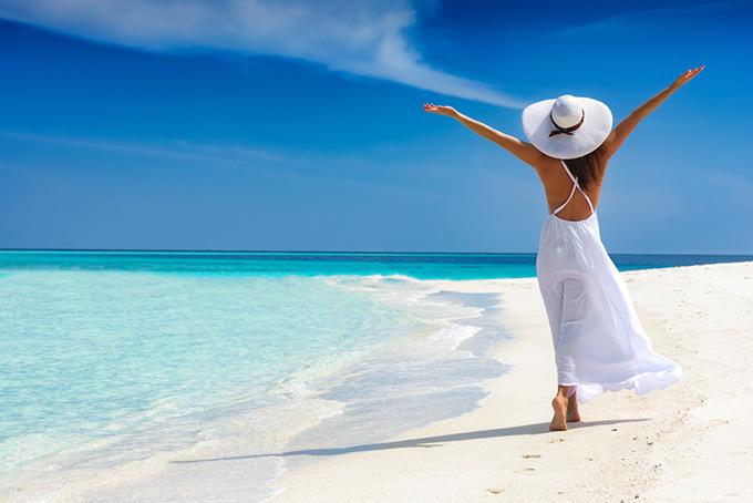 海辺で両手を広げている女性の画像