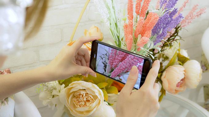 スマートフォンで花を撮影している手元