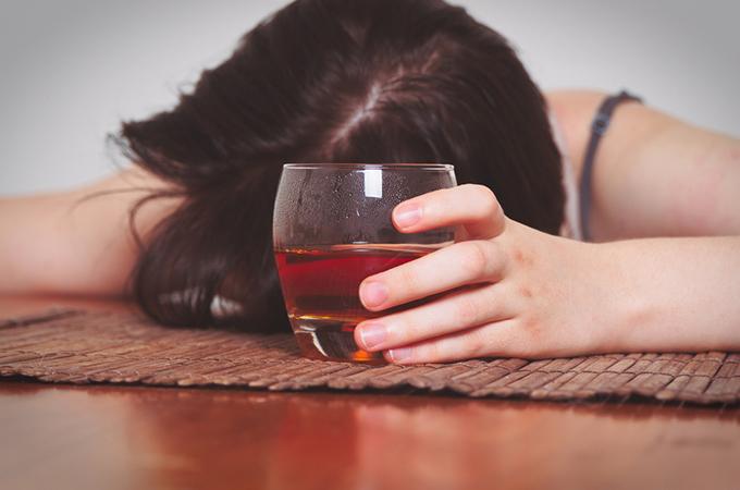 お酒を飲んで酔い潰れている女性の画像