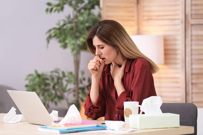 室内で咳をしている女性の画像