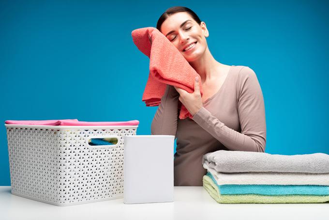 タオルを頬に当てて微笑む女性の画像