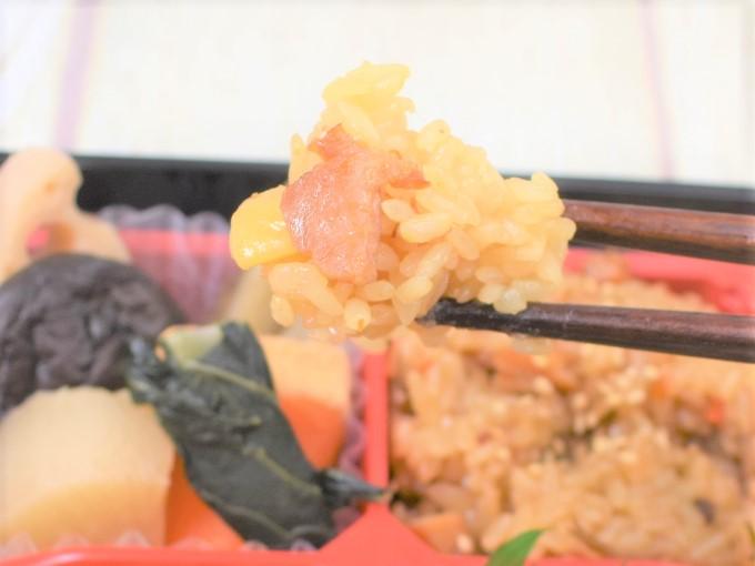 箸で持ち上げた「2種のおこわ弁当(阿波尾鶏と栗)」の画像