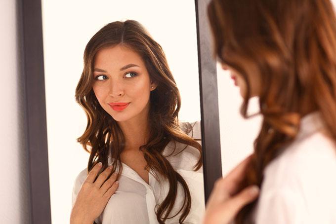 鏡に全身を映す女性の画像