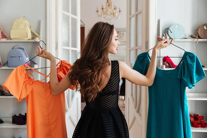 洋服を比べる女性の画像