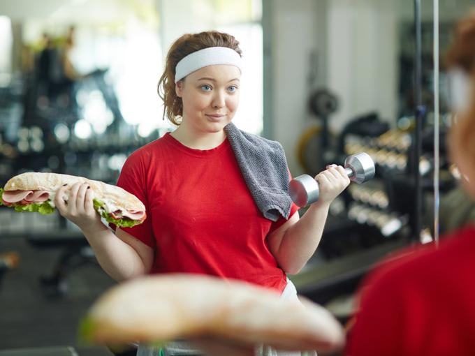 ダンベルの替わりに片手に大きなサンドイッチを持ちながら、運動する女性