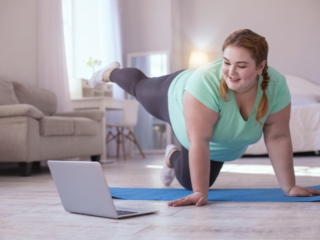 動画を見ながらエクササイズに励む女性