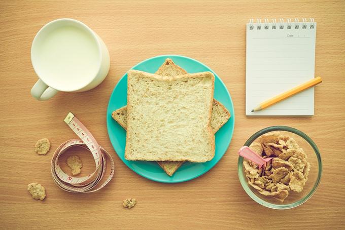 スライスした食パン、シリアル、ミルク、メモ帳などのイメージ画像