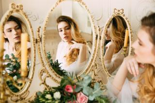 女性が鏡を見ている写真