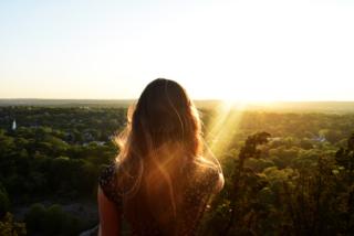 女性が夕陽を見ている写真