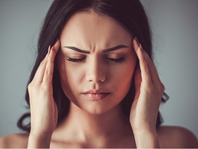 頭を押さえつらい頭痛に苦しむ女性
