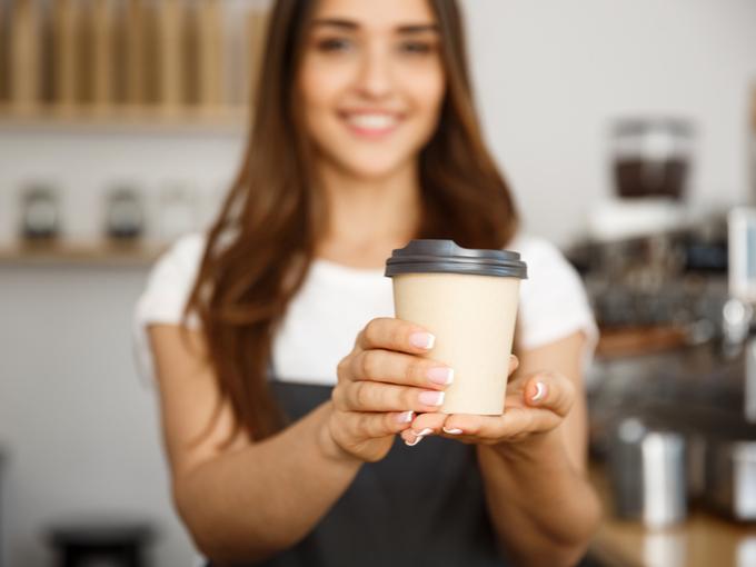 女性がコーヒーを手渡している画像