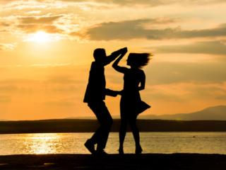 海岸で手をとり合うカップル