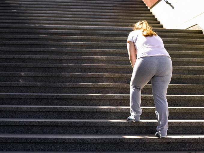 階段をゆっくりした足取りで上る肥満女性