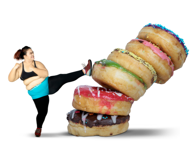 重なった巨大なドーナツと闘う肥満女性