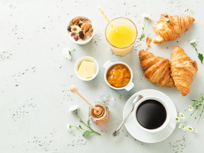 クロワッサンやジュースなどが並んだ朝食