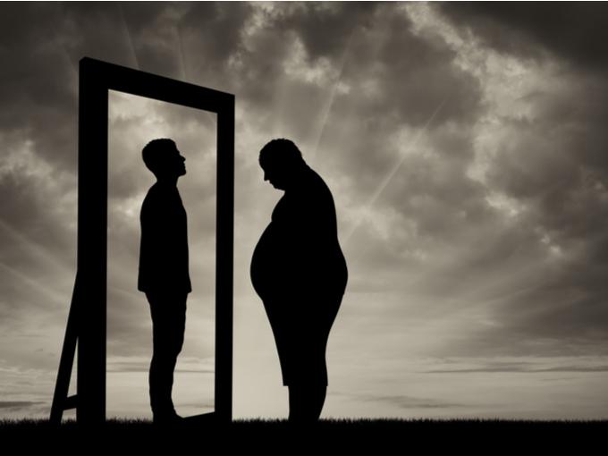 鏡に映った理想的な体型をイメージしている肥満体型の男性