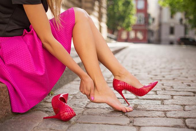 道端でヒールを脱いで足を押さえている女性の画像