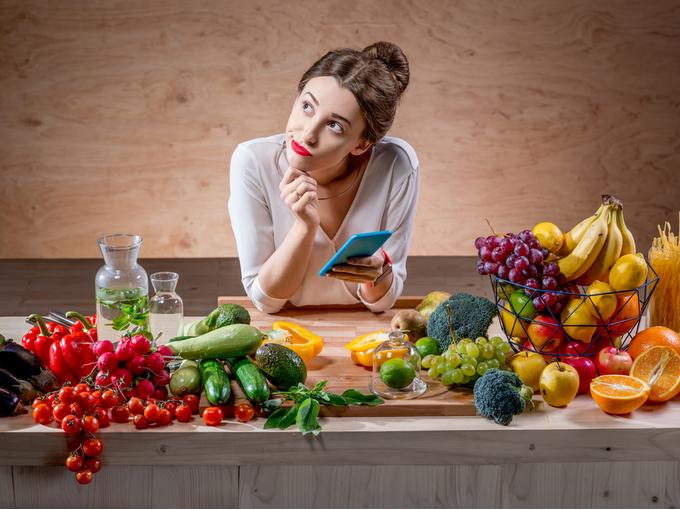 たくさんの果物や野菜に囲まれてカロリーを考える女性