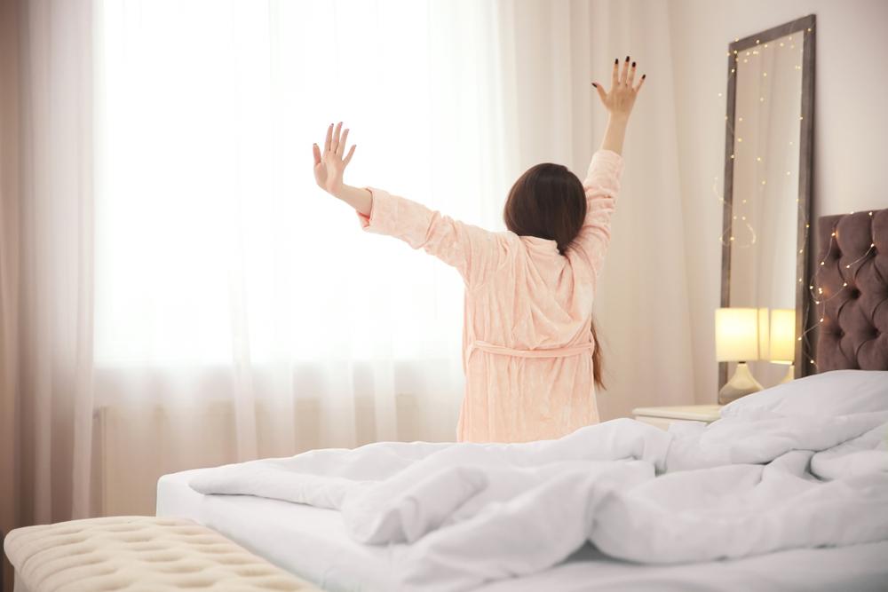 手をあげて伸びをしているベットから起床した女性