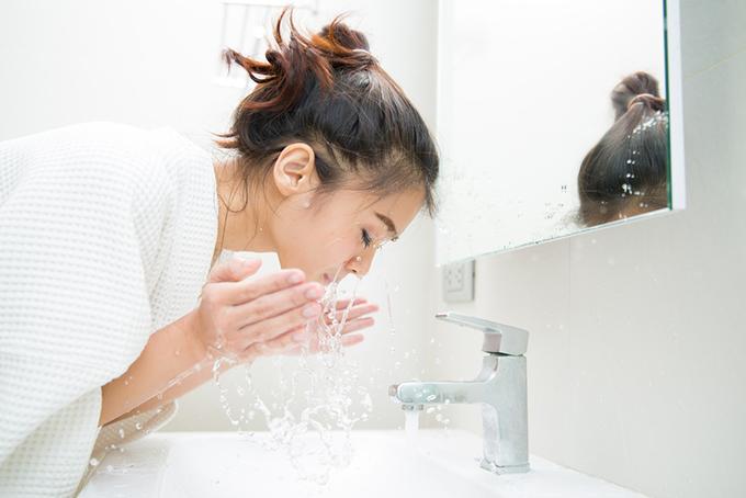 水で顔を洗っている女性