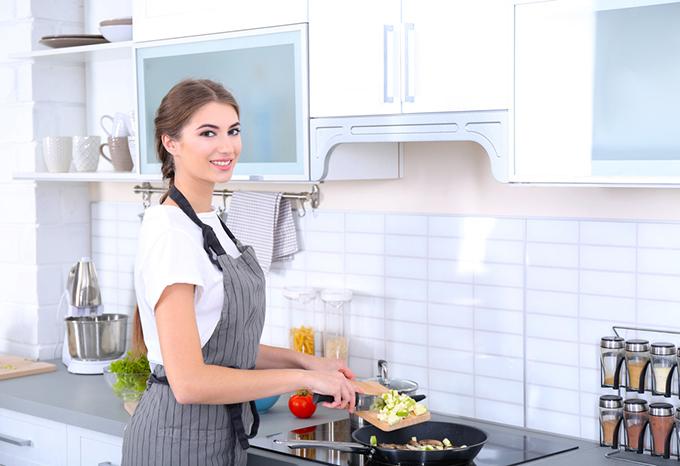 コンロの前で料理している女性の画像