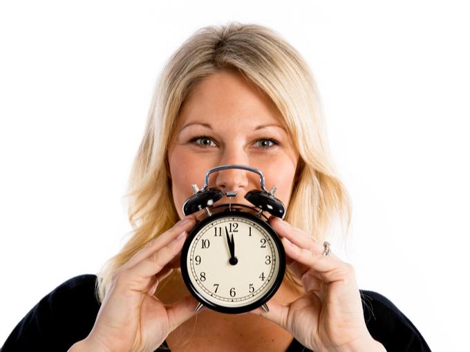 体内リズムをイメージして時計をもつ女性