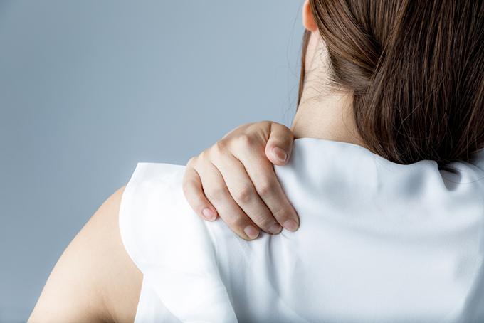 肩をおさえる女性の画像