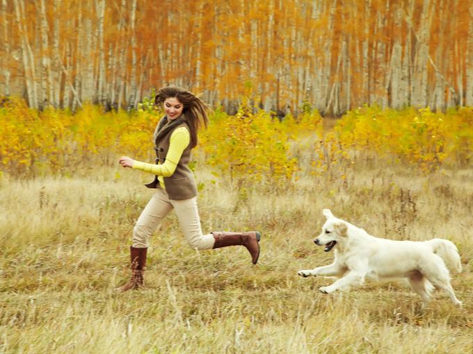 犬と一緒に自然の中を走る女性