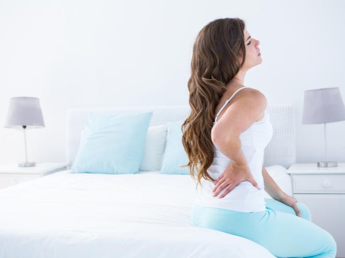 腰に痛みを感じる女性