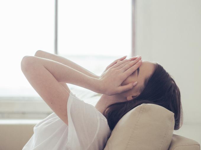 ソファーに座って顔を押さえる女性