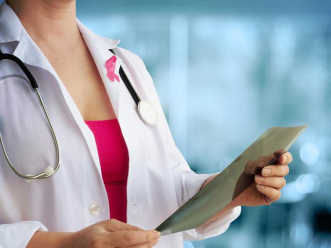 白衣にピンクリボンをつけて診察を行う女性医師