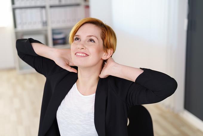 頭を両手で支えて上を見る女性の画像