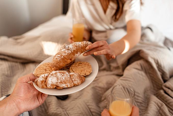 お皿にのったパンを取ろうとしている女性の手もと