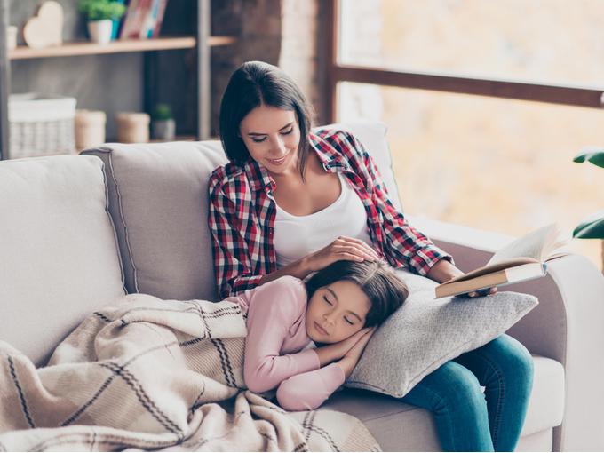 母親の膝枕で昼寝する子ども